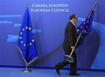 Funcionário ajusta bandeiras na entrada da sede do Conselho da UE para cúpula de líderes do bloco para discutir orçamento de longo prazo em Bruxelas, Bélgica. Líderes da UE iniciam nesta quinta-feira uma discussão orçamentária sob pressão para evitar alguns notórios erros do passado. 22/11/2012 REUTERS/Yves Herman