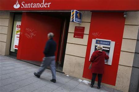 A woman uses an ATM machine at a Santander bank branch in Madrid October 16, 2012. REUTERS/Susana Vera (SPAIN - Tags: BUSINESS)
