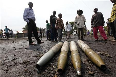 People gather around tank shells abandoned by fleeing Congolese army in Ndosho near Goma November 21, 2012. REUTERS/James Akena (DEMOCRATIC REPUBLIC OF CONGO - Tags: CIVIL UNREST POLITICS)