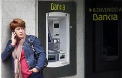 Madrid, una donna al telefono accanto a un bancomat di Bankia, in una foto del 26 ottobre. REUTERS/Sergio Perez