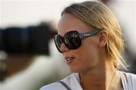 Denmark's professional tennis player Caroline Wozniacki looks on near the 18th green during the first round of the DP World Tour Championship at Jumeirah Golf Estates in Dubai, November 22, 2012. Wozniacki is the girlfriend of golfer Rory McIlroy of Northern Ireland. REUTERS/Nikhil Monteiro