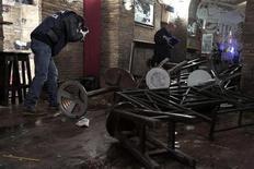 Un poliziotto valuta i danni in un pub romano dopo scontri tra tifosi. REUTERS/Yara Nardi