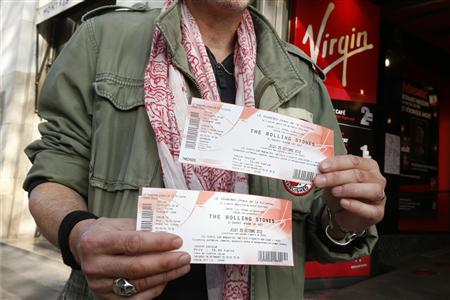 A Rolling Stones fan displays two tickets he purchased for a short warm-up gig in Paris October 25, 2012 as the group prepares for a series of 50th anniversary concerts later this year. REUTERS/Benoit Tessier