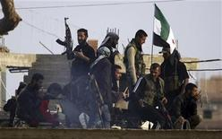 Members of the Free Syrian Army are pictured in the northern Syrian town of Ras al-Ain, as seen from the Turkish border town of Ceylanpinar, Sanliurfa province, November 22, 2012. NATO ambassadors met on Wednesday to consider a Turkish request for the deployment of Patriot missiles near its border with Syria as the conflict in its southern neighbour deepens. A Reuters photographer said sporadic gunfire was heard throughout the day at the border. REUTERS/Amr Abdallah Dalsh (TURKEY - Tags: POLITICS CONFLICT MILITARY)