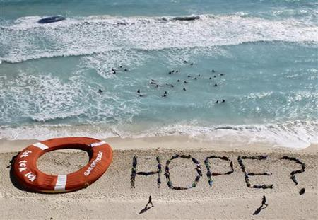 Activists of Environment Greenpeace perform next to a giant life ring, during talks on climate change, in Cancun beach December 10, 2010. REUTERS/Henry Romero/Files
