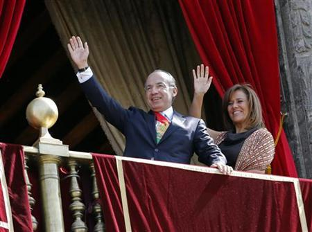 Mexico's President Felipe Calderon (L) and his wife and Mexico's first lady Margarita Zavala, wave to the crowd after presiding for the last time over a military parade in celebration of the 102nd anniversary of the Mexican Revolution on Zocalo Square in Mexico City November 20, 2012. REUTERS/Bernardo Montoya