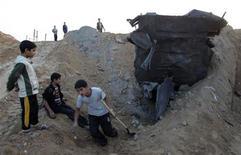 Metidos hasta las rodillas en los cráteres abiertos por los ataques aéreos israelíes, los palestinos han cogido palas y sacos de arena para reabrir los túneles que utilizan para introducir mercancías desde Egipto a Gaza, mientras las agencias humanitarias se apresuraban a reponer los menguados suministros de Gaza. En la imagen, un joven palestino con una pala trabaja para reparar un tunel de contrabando dañado en el sur de la Franja de Gaza, cerca de la frontera con Egipto, el 22 de noviembre de 2012. REUTERS/Ibraheem Abu Mustafa