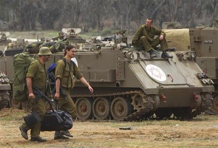 Israeli soldiers carry their gear past an armoured personnel carrier (APC) as they head home near the border with the northern Gaza Strip November 22, 2012.A ceasefire between Israel and Hamas took hold on Thursday with scenes of joy among the ruins in Gaza over what Palestinians hailed as a victory, and both sides saying their fingers were still on the trigger. REUTERS/Ronen Zvulun