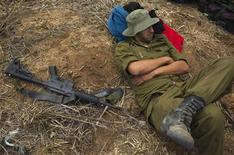 An Israeli reservist soldier rests beside a weapon as he waits in a field before heading home, near the border with the northern Gaza Strip November 22, 2012. A ceasefire between Israel and Hamas took hold on Thursday with scenes of joy among the ruins in Gaza over what Palestinians hailed as a victory, and both sides saying their fingers were still on the trigger. REUTERS/Ronen Zvulun