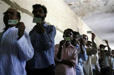 Men hold up their identification cards for local television cameras covering a polling station in Karachi October 17, 2010. REUTERS/Athar Hussain/Files