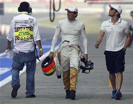 HRT Formula One driver Pedro de la Rosa (C) of Spain walks in the pit lane at the Buddh International Circuit in Greater Noida, on the outskirts of New Delhi, October 26, 2012. REUTERS/Vivek Prakash/Files