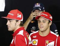 O piloto da Ferrari Fernando Alonso (E) passa por seu companheiro de equipe, Felipe Massa (D), com o alemão Sebastian Vettel atrás durante entrevista no circuito de Interlagos, em São Paulo, nesta quinta-feira. REUTERS/Sergio Moraes