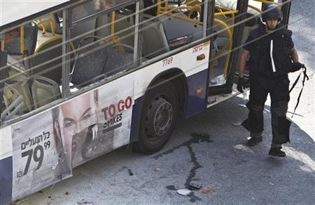 An Israeli police explosives expert walks next to a damaged bus at the scene of an explosion in Tel Aviv November 21, 2012. REUTERS/Nir Elias