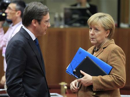 Portugal's Prime Minister Pedro Passos Coelho (L) talks with Germany's Chancellor Angela Merkel (R) during an European Union leaders summit discussing the European Union's long-term budget in Brussels November 22, 2012. European Union negotiators believe they are close to securing British and German backing for a deal on nearly a trillion euros of spending over the next seven years, but last minute concessions may be needed to secure French and Polish support. REUTERS/Yves Herman