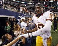 Washington Redskins quarterback Robert Griffin III shakes hands with fans after the Redskins beat the Dallas Cowboys in their NFL football game in Arlington, Texas November 22, 2012. REUTERS/Mike Stone