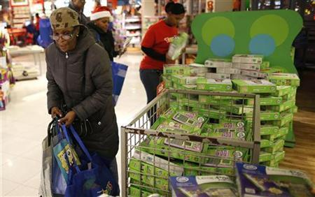 A woman, among the first shoppers in a Toys R Us store, shop on Thanksgiving Day in Times Square, New York November 22, 2012. REUTERS/Carlo Allegri