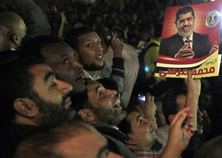 People carry a poster of Egyptian President Mohamed Mursi as they gather in front of the general prosecutor's office in support of Mursi's decision to sack Abdel Maguid Mahmoud, in Cairo November 22, 2012. REUTERS/Mohamed Abd El Ghany