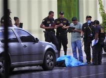 Hombres armados vestidos de policías asesinaron el jueves a siete personas en un hospital privado en Guatemala, en un ataque que tenía como objetivo a un presunto narcotraficante que logró escapar del tiroteo, dijeron autoridades. En la imagen, responsables policiales junto al cadáver de un hombre, una de las víctimas del tiroteo en Guatemala, el 22 de noviembre de 2012. REUTERS/Jorge Dan López