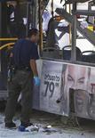 Las autoridades israelíes arrestaron a un árabe-israelí bajo sospechas de colocar una bomba en un autobús de Tel Aviv que hirió a 15 personas horas antes de que se acordara un alto el fuego con Hamás en Gaza, dijeron el jueves la policía y responsables de seguridad. En la imagen, un experto en explosivos de la policía israelí examina el autobús atacado en Tel Aviv, el 21 de noviembre de 2012. REUTERS/Nir Elias