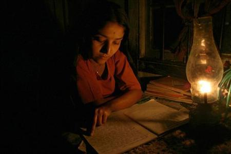 A girl studies by kerosene lamp due to a power cut-off in the remote village of Lingsey, about 157 km (98 miles) from Siliguri, February 26, 2006. REUTERS/Rupak De Chowdhuri/Files