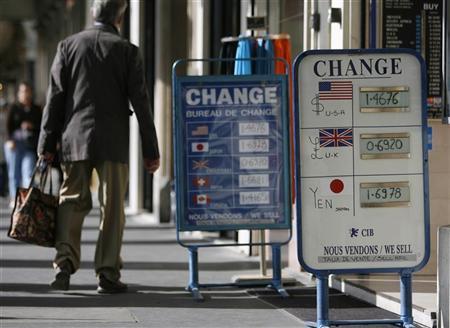 A man walks past signs outside a currency exchange bureau in Paris September 24, 2007. REUTERS/Vincent Kessler