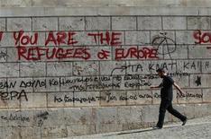 Мужчина проходит мимо стены с граффити недалеко от Афинской Академии 24 сентября 2012 года. Международные кредиторы согласовали новые меры сокращения греческого долга, но им осталось найти 10 миллиардов евро ($13 миллиардов), чтобы получить одобрение Международного валютного фонда на перевод средств, сообщил в пятницу представитель греческого правительства. REUTERS/John Kolesidis