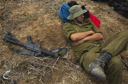 An Israeli reservist soldier rests beside a weapon as he waits in a field before heading home, near the border with the northern Gaza Strip November 22, 2012. REUTERS/Ronen Zvulun