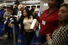 """Люди стоят в очереди в кассу в магазине Toys R Us в Нью-Йорке в День благодарения 22 ноября 2012 года. В США наступила """"черная пятница"""": с вчера четверга американские """"шопоголики"""" выстроились в длинные очереди у прилавков магазинов в поисках выгодных предложений, дав старт рождественскому сезону распродаж. REUTERS/Carlo Allegri"""