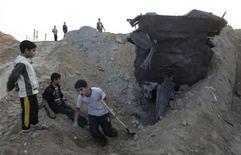 Ragazzi palestinesi cercano di sistemare un tunnel danneggiato dai bombardamenti israeliani nella parte meridionale di Gaza, vicino al confine con l'Egitto. REUTERS/Ibraheem Abu Mustafa