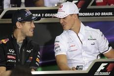 El campeón de la Fórmula Uno, Sebastian Vettel, alabó a su compatriota Michael Schumacher al que calificó como el héroe de su infancia mientras la leyenda alemana preparaba su segunda despedida de la competición en el Gran Premio de Brasil este domingo. En la imagen, Vettel y Schumacher conversan en la rueda de prensa de los piltos en Interlagos, el 22 de noviembre de 2012 en Sao Paulo. REUTERS/Sergio Moraes