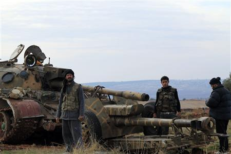 Free Syrian Army fighters pose near a tank after they said they fought and defeated government troops at military base at the town of Atareb near Aleppo November 19, 2012. Picture taken November 19, 2012. REUTERS/Omar Ezzdin/Shaam News Network/Handout