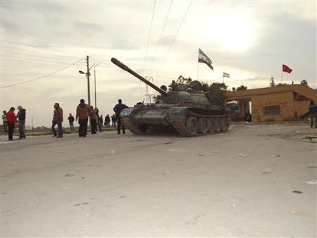 Residents and Free Syrian Army fighters pose near a tank after the fighters said they fought and defeated government troops from the town of Ras al-Ain, near the province of Hasaka, 600 km (375 miles) from Damascus, November 22, 2012. REUTERS/Samer Abdullah/Shaam News Network/Handout