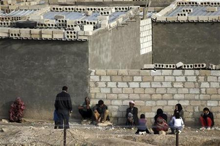 Syrians take cover in front of their home in the northern Syrian town of Ras al-Ain during gunfire, as seen from the Turkish border town of Ceylanpinar, Sanliurfa province, November 22, 2012. REUTERS/Amr Abdallah Dalsh