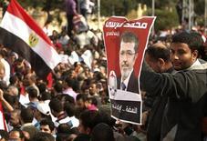 Apoiador do presidente egípcio Mohamed Mursi carrega poster com imagem de Mursi, enquanto outros cantam slogans pró-Mursi durante manifestação em frente ao Palácio Presidencial no Cairo. Mursi levantou controvérsias com um decreto divulgado na quinta-feira, que amplia seus próprios poderes. 23/11/2012 REUTERS/Asmaa Waguih