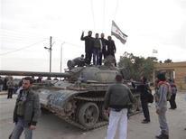 Más de 40.000 personas perdieron la vida en los 20 meses de conflicto entre las fuerzas del presidente sirio, Bashar el Asad, y los rebeldes que buscan deponerlo, dijo el viernes un grupo de observadores de la violencia. En la imagen, combatientes del Ejército Libre Sirio posan en un tanque después de decir que habían derrotado y expulsado a tropas gubernamentales en la ciudad de Ras al-Ain, cerca de la provincia de Hasaka, a 600 km de Damasco, el 22 de noviembre de 2012. REUTERS/Samer Abdullah/Shaam News Network/