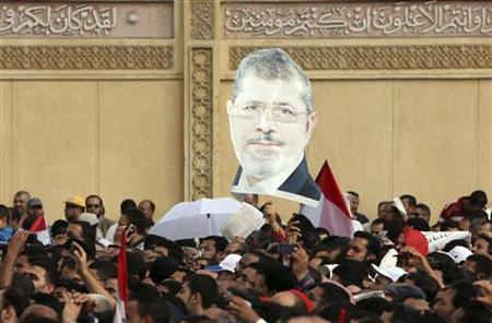 Supporters of Egyptian President Mohamed Mursi chant pro-Mursi slogans and carried an image of Mursi, during a protest praising a new decree he issued on Thursday, in front of the presidential palace in Cairo November 23 , 2012. REUTERS/Asmaa Waguih