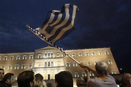 REFILE - CORRECTING HEADLINE A protestor waves Greek flag in front of the parliament in Syntagma square during a 48-hour strike by the two major Greek workers unions in central Athens November 7, 2012. REUTERS/John Kolesidis (GREECE - Tags: CIVIL UNREST POLITICS BUSINESS EMPLOYMENT)