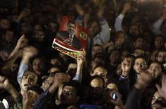 El decreto del presidente de Egipto, Mohamed Mursi, para evitar que sus decisiones sean desafiadas por la justicia hasta que sea electo un nuevo Parlamento desató el viernes la furia de sus opositores, quienes lo acusaron de ser un nuevo Hosni Mubarak y de apoderarse de la revolución. En la imagen, manifestantes portan un poster del presidente Mohamed Mursi en una concentración en apoyo del decreto Mursis, en El Cairo, el 22 de noviembre de 2012. REUTERS/Mohamed Abd El Ghany