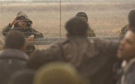An Israeli soldier gestures as Palestinians stand close to the fence between Israel and the southern Gaza Strip November 23, 2012. REUTERS/ Ibraheem Abu Mustafa