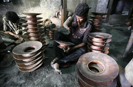 Workers use hammers to form copper pots inside a workshop in Ahmedabad February 2, 2011. REUTERS/Amit Dave/Files