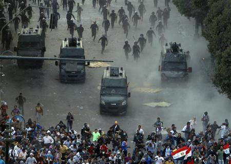 Protesters run from riot police during clashes at Tahrir square in Cairo November 23, 2012. REUTERS/Mohamed Abd El Ghany