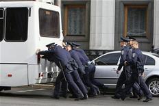 Украинские полицейские толкают автобус, сломавшийся в центре Киева 2 октября 2012 года. Госбанк помог Киеву погасить евробонды на $250 млн. REUTERS/Gleb Garanich