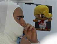 La escudería Sauber confirmó el viernes al mexicano Esteban Gutiérrez, de 21 años, como piloto oficial para la temporada 2013 de la Fórmula Uno. En la imagen, el piloto Esteban Gutiérrez se ajusta su pasamontañas antes de la primera sesión práctica para el Gran Premio de la India, en las afueras de Nueva Delhi, el 26 de octubre de 2012. REUTERS/Vivek Prakash