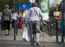 An elderly woman walks on a stick along a shopping street in Berlin, September 3, 2012. Labour Minister Ursula von der Leyen has called for a pension subsidy for low-income earners to avoid widespread old-age poverty after 2030 in Germany's increasingly aging society. REUTERS/Thomas Peter (GERMANY - Tags: POLITICS SOCIETY)