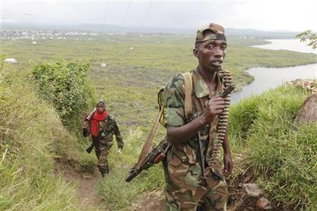 Congolese Revolutionary Army (CRA) fighters walk toward their position near Sake 27km (16 miles) north of Goma, in eastern Congo November 23, 2012. Rebels in eastern Congo pushed south along Lake Kivu on Friday after repelling a counter-attack by government forces near the new rebel stronghold in the city of Goma on the Rwandan border. Others moved north from the strategic road junction at Sake. REUTERS/James Akena (DEMOCRATIC REPUBLIC OF CONGO - Tags: CIVIL UNREST POLITICS CONFLICT)