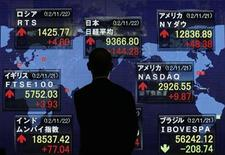 A man looks at stock index board showing various countries stock price index outside a brokerage in Tokyo November 22, 2012. Japan's Nikkei average climbed 1.6 percent to a 6-1/2-month closing high on Thursday, boosted by gains in automakers and electronics companies on expectations that a sharply weaker yen will boost their earnings. REUTERS/Kim Kyung-Hoon (JAPAN - Tags: BUSINESS)