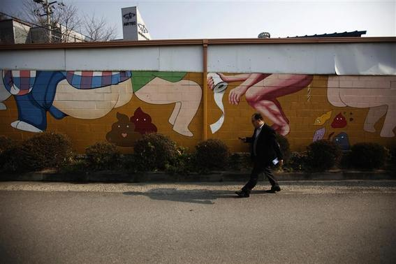 A man walks past a mural as he uses his phone at the Toilet Culture Park in Suwon, about 46 km (29 miles) south of Seoul, November 22, 2012. The park, which is the only one of its type in the world, exhibits a variety of bowls from Korean traditional squat toilets to western bedpans. REUTERS/Kim Hong-Ji