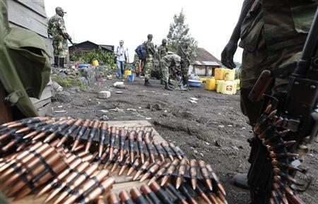 A Congolese Revolutionary Army (CRA) fighter stands next to a pile of bullets November 23, 2012, abandoned by fleeing government soldiers early this week as they capture Goma in the Democratic Republic of Congo. REUTERS/James Akena