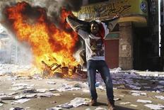 Egitto, un dimostrante festeggia davanti alla sede devastata dei Fratelli Musulmani ad Alessandria, oggi. REUTERS/Stringer