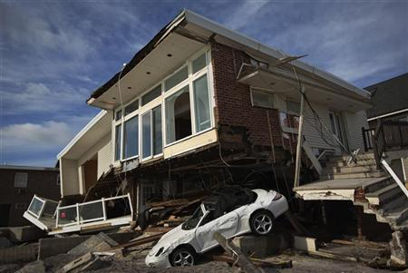 An automobile sits under a home damaged by superstorm Sandy in the Belle Harbor section of the Queens borough of New York November 14, 2012. REUTERS/Shannon Stapleton